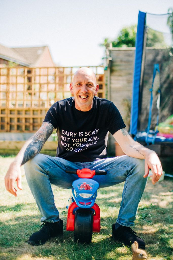 Vegan mentor John Awen sitting on a children's bike
